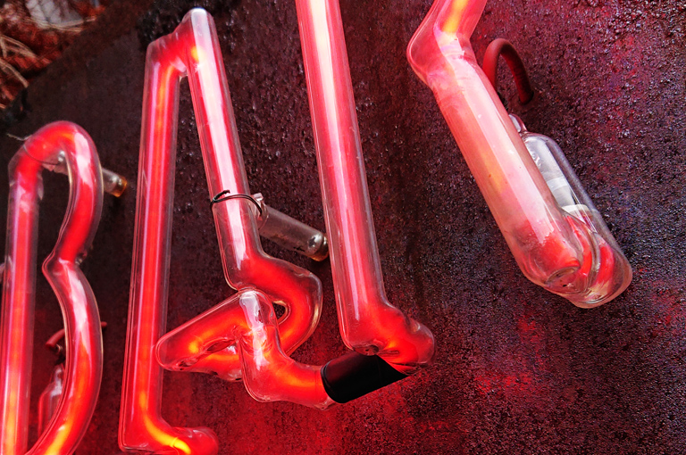 Norneón rótulo banderola a dos caras oxidada e iluminada mediante luz de neón